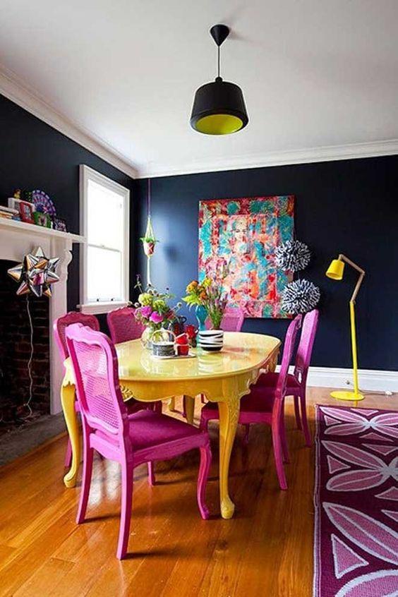 Parede de sala decorada na cor azul marinho com quadro colorido e móveis nas mesmas tonalidades