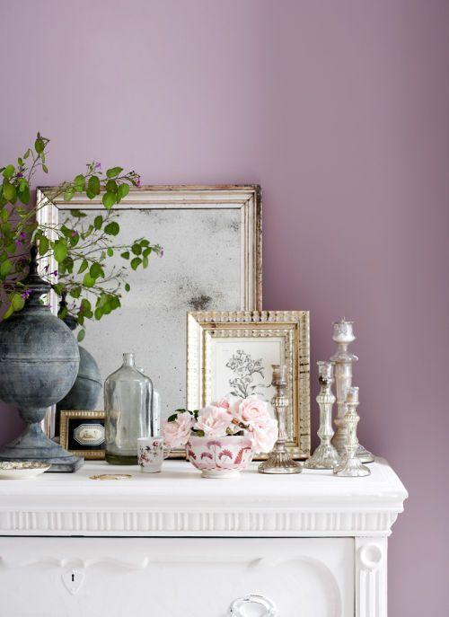 Parede de sala decorada na cor lilás com móveis brancos e quadros com moldura dourada
