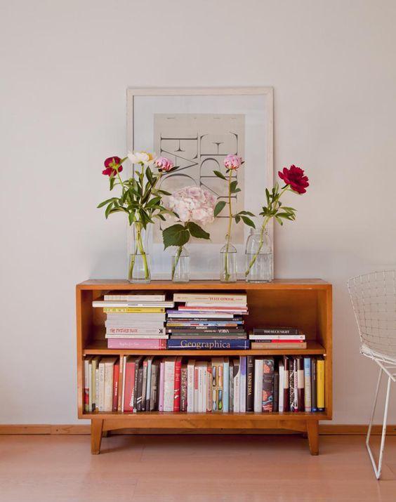 Parede de sala pequena decorada com quadros e uma mini estante de livros