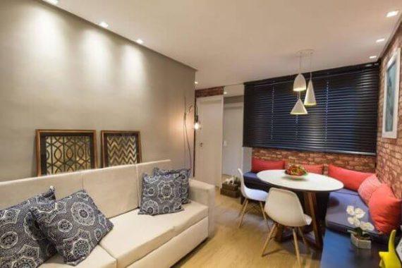 Parede decorada para sala com cimento queimado e quadros apoiados no sofa
