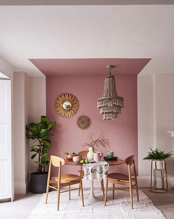 Parede decorada para sala de jantar com pintura setorizada em tons de rosa e espelhos pendurados