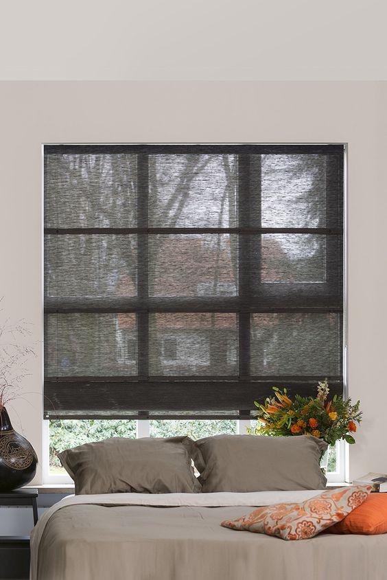 Quarto com persiana preta na janela atrás da cama
