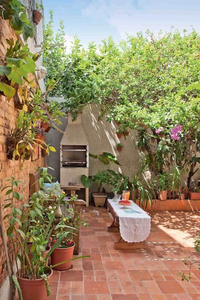 Quintal pequeno com chaminé de churrasqueira e plantas na decoração