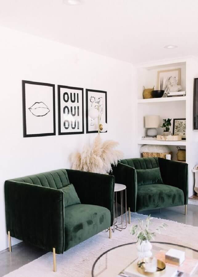 Sala branca decorada com quadros preto e branco e poltrona verde escuro confortável