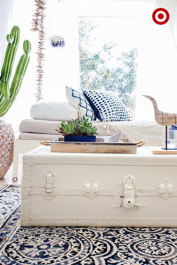 Sala clean com bau de madeira branco e almofadas azuis