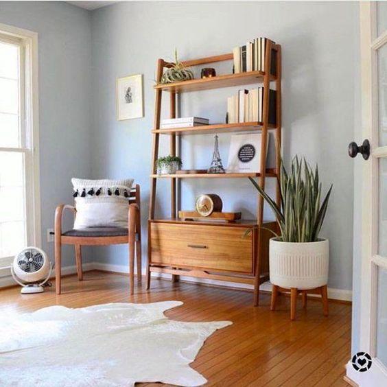 Sala com estante cavalete de madeira e plantas