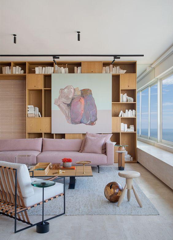 Sala com estante de livros e sofá rosa