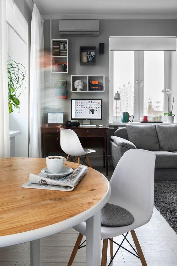 Sala com home office pequeno ao lado do sofa