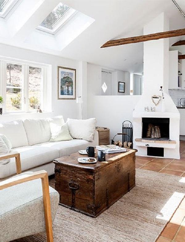 Sala com lareira e bau de madeira e tapete bege