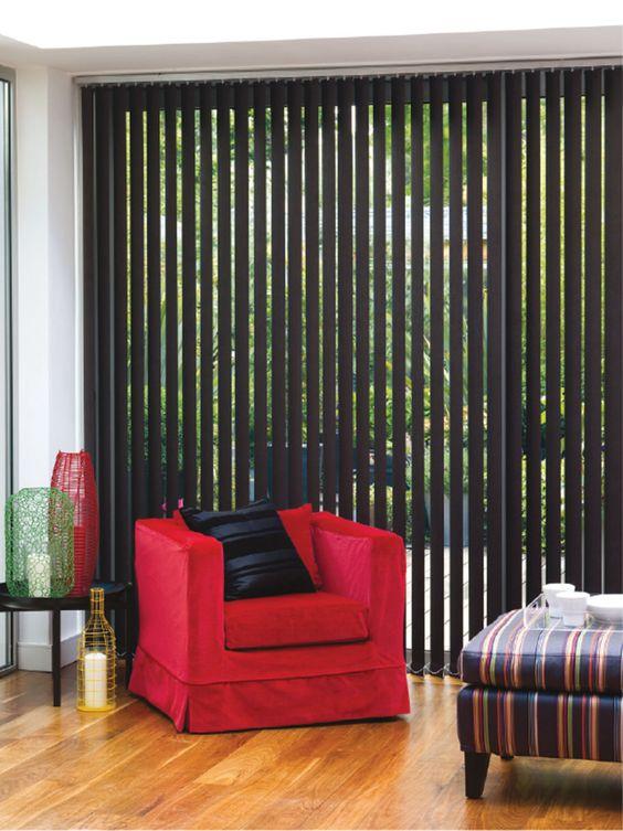 Sala com persiana vertical preta e poltrona vermelha