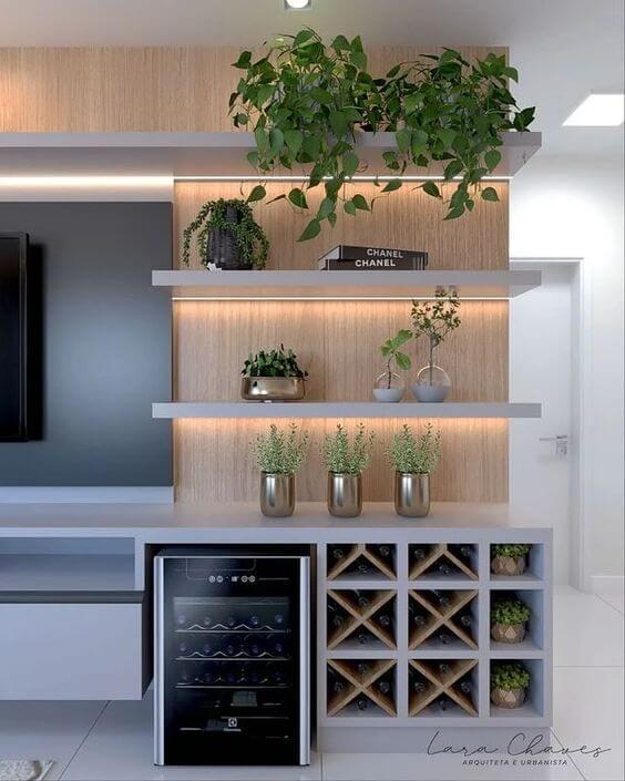 Sala de TV com parede decorada com prateleiras e mini bar