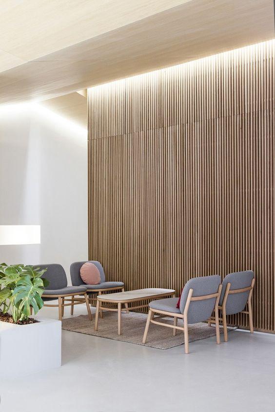 Sala de espera com cadeiras confortáveis em cinza e almofadas redondas