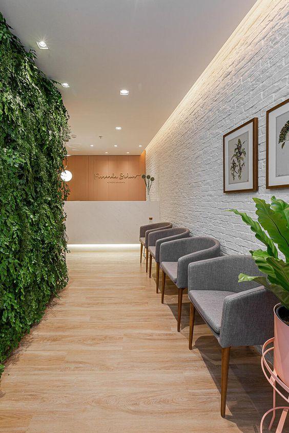 Sala de espera com cadeiras na cor cinza e parede verde