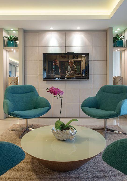 Sala de espera com poltronas azuis e tv