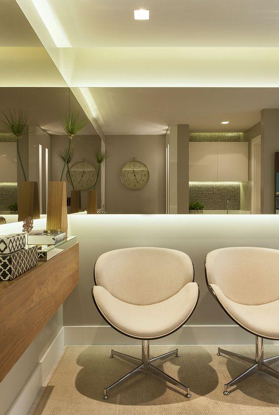 Sala de espera com poltronas brancas e espelho ao redor do espaço