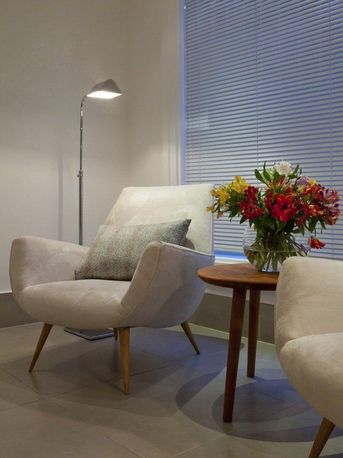 Sala de espera com poltronas cinza e mesa de centro com vaso de plantas