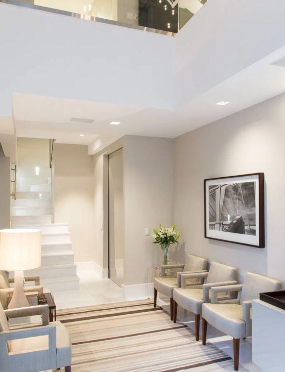 Sala de espera com poltronas confortáveis e paleta de cores suave