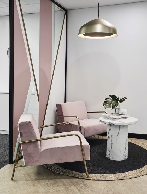 Sala de espera com poltronas cor de rosa e mesa de centro marmorizada com revistas e vaso de plantas