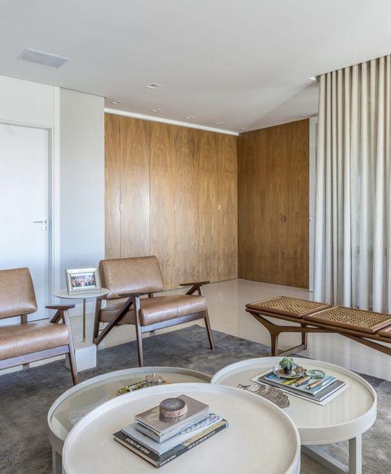 Sala de espera com poltronas de couro e mesa de centro redonda
