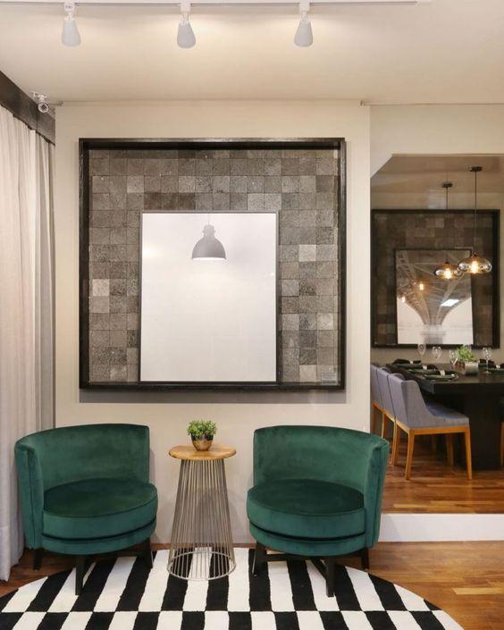 Sala de espera com poltronas verdes e quadro moderno na parede