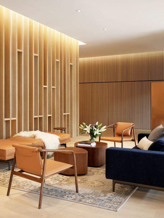 Sala de espera com sofá azul marinho cadeiras de madeira e chaise de couro
