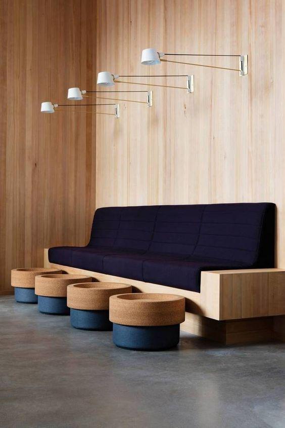 Sala de espera com sofá azul marinho e estrutura de madeira