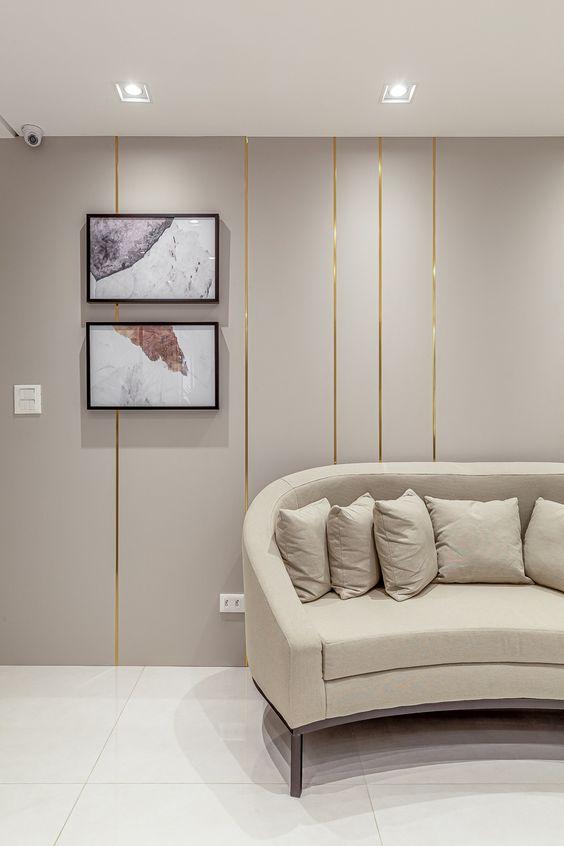 Sala de espera chique com sofá redondo bege e papel de parede dourado