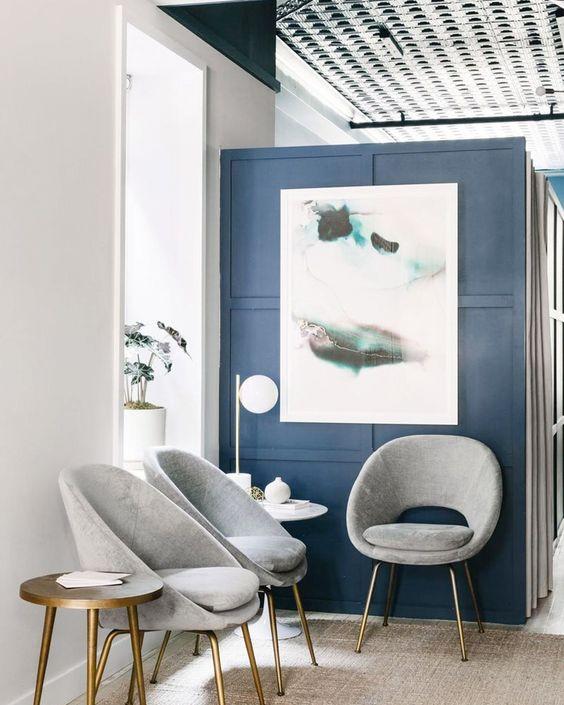 Sala de espera moderna com cadeiras cinza e parede azul