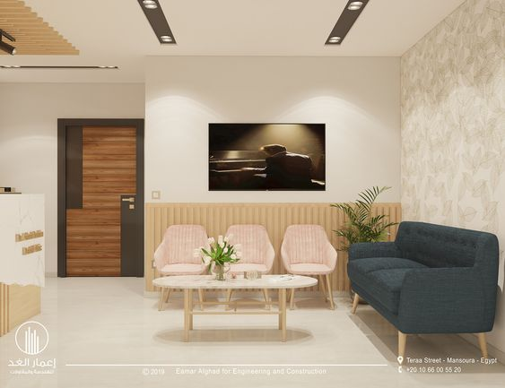 Sala de espera pequena com sofá azul e cadeiras pequena