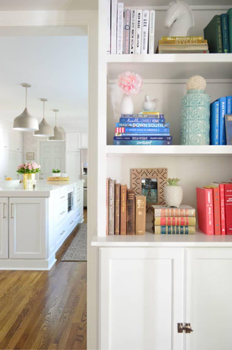 Sala de estar branca com enfeites para estante coloridos