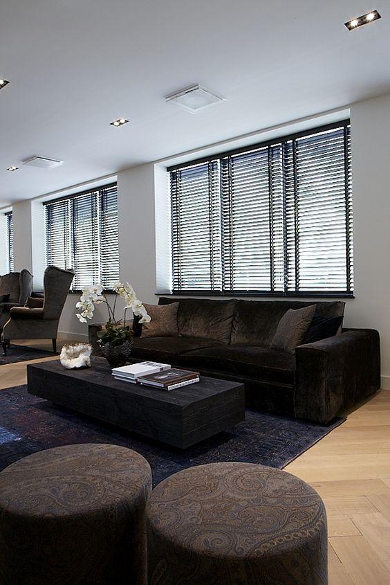 Sala de estar com sofá marrom e persiana preta