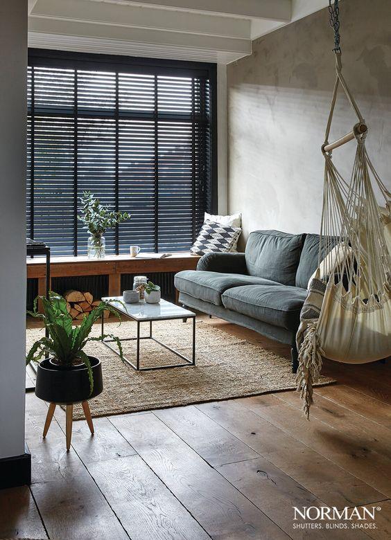 Sala de estar pequena com persiana preta e sofá cinza