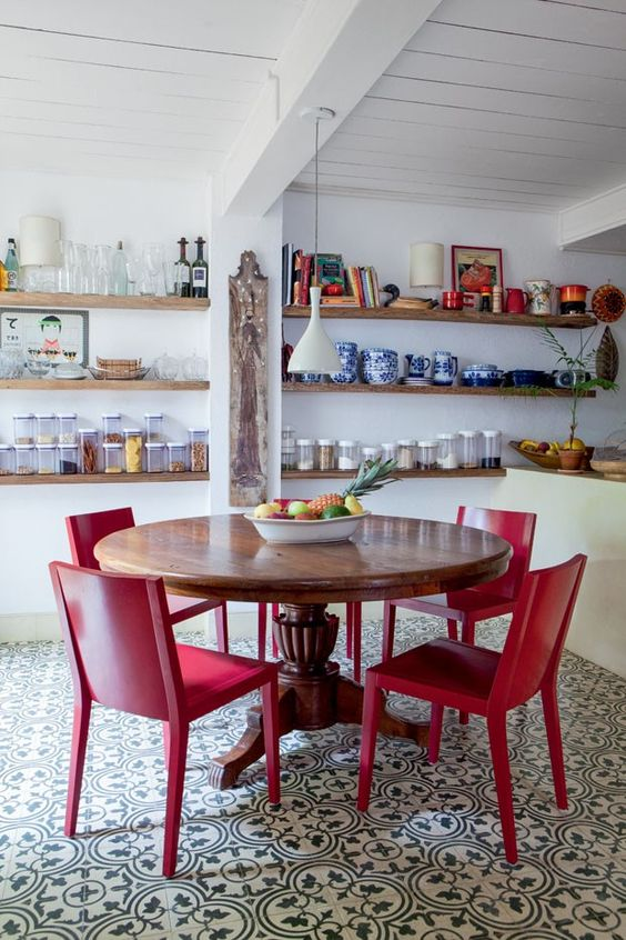 Sala de jantar com mesa de madeira e cadeira vermelha