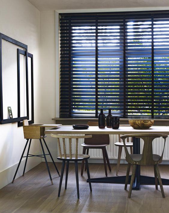 Sala de jantar com persiana preta e móveis de madeira