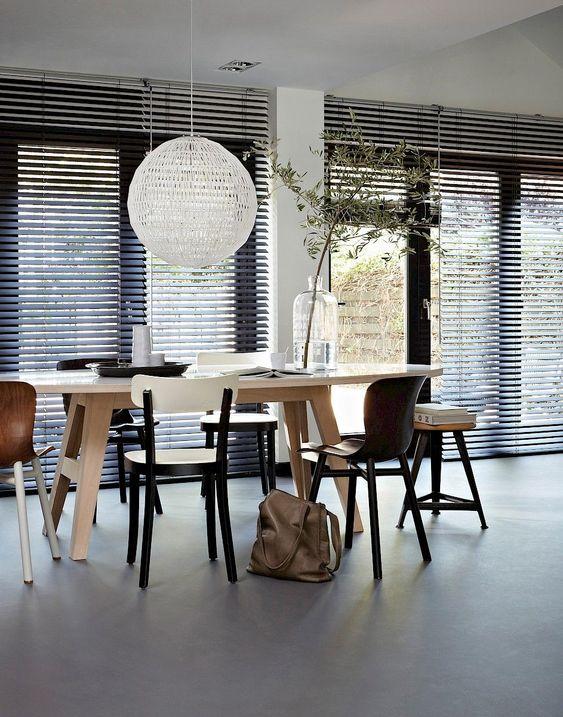 Sala de jantar com persiana preta e móveis de madeira modernos