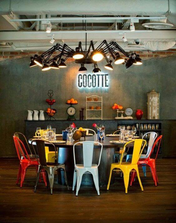 Sala de jantar grande decorada com cadeira de ferro colorida