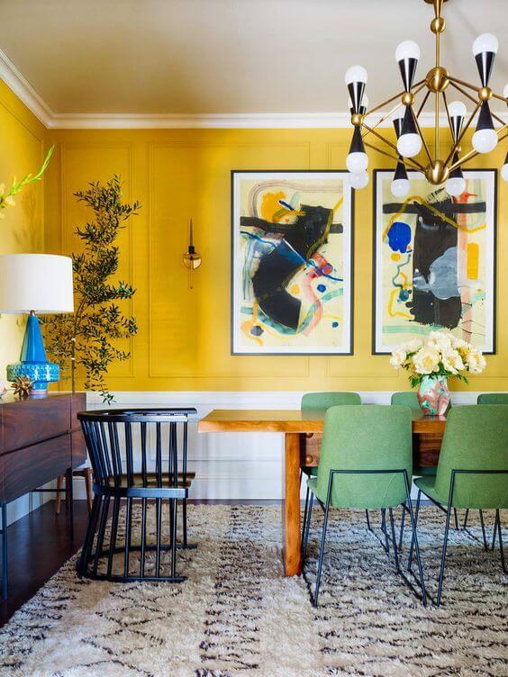 Sala de jantar grande decorada com tons de amarelo com cadeira retrô verde