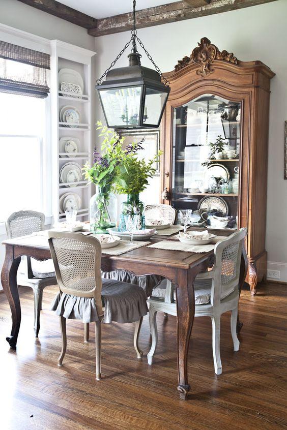 Sala de jantar rústica com mesa provençal e cristaleira de madeira