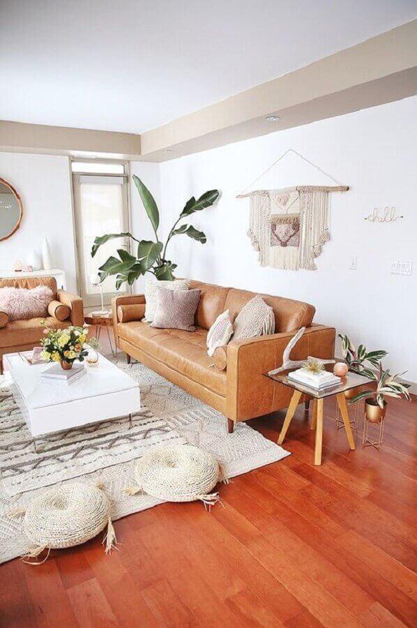 Sala grande decorada com chão de madeira sofá caramelo e plantas