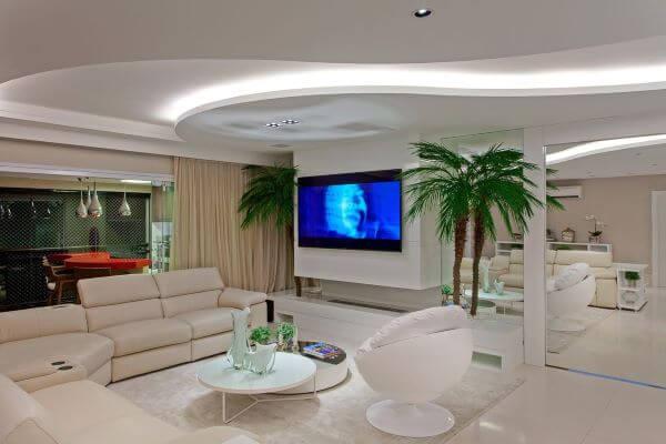 Sala grande decorada com lareira e tons neutros chique