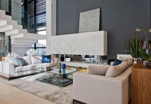 Sala grande decorada com móveis claros e enfeites azuis