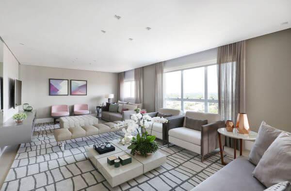Sala grande decorada com móveis confortáveis e um toque de cor nos quadros e poltronas
