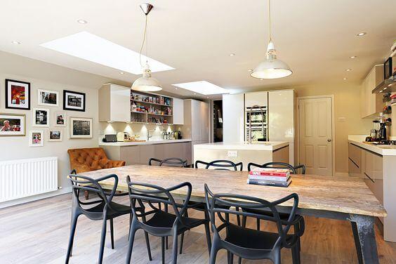 Sala grande decorada com mesa de madeira e cadeira allegra