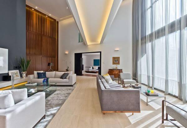 Sala grande decorada com pé direito alto iluminada e decorada com móveis claros