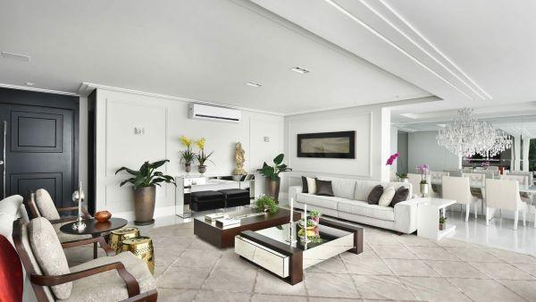 Sala grande decorada com sofá branco e mesa de centro espelhada