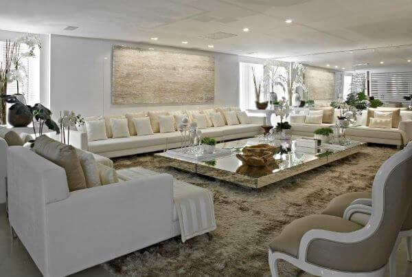Sala grande decorada com sofás bege e mesa de centro espelhada
