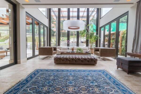 Sala grande decorada com tapete e móveis confortaveis e pé direito alto