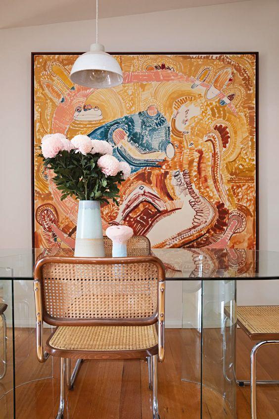 Sala moderna com cadeira de palha e parede decorada com quadro