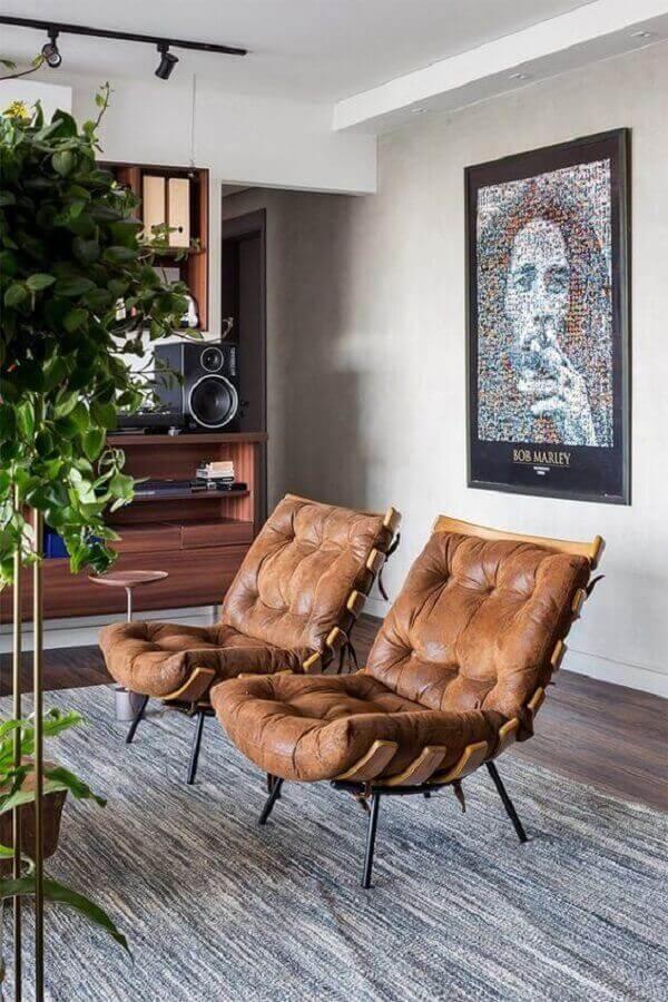 Sala moderna decorada com quadros de famosos e poltronas em couro