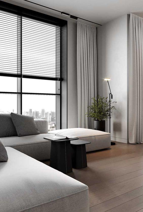 Sala neutra com persiana preta e sofá cinza